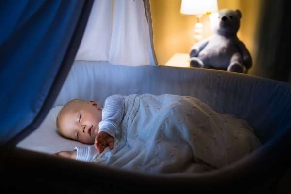 baby in bassinet in room lit by lamp