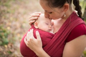 Babywearing mom and baby outside, kiss on forehead