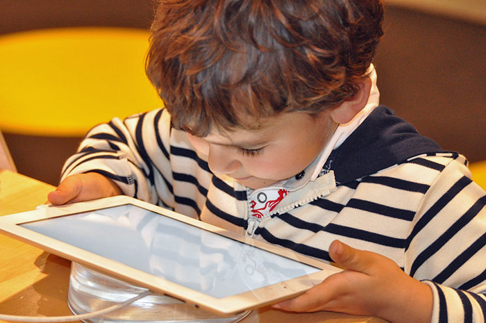 Young child with tablet - how to raise children in the digital era