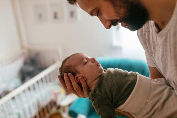 dad putting sleeping baby into crib
