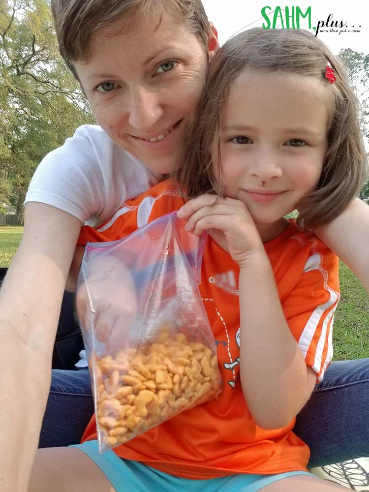 big girl at soccer practice with bag of brandless organic cheese duck crackers non-gmo snacks