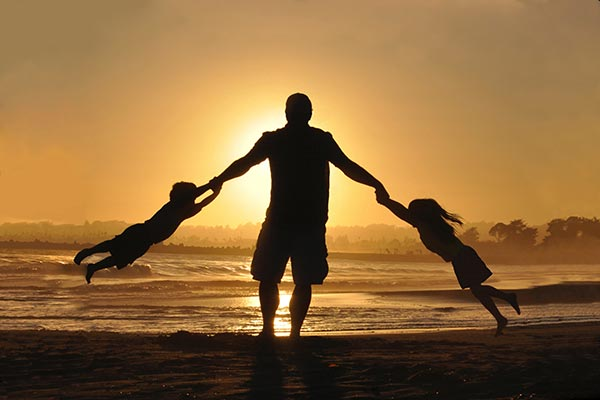 father playing with kids in sunset