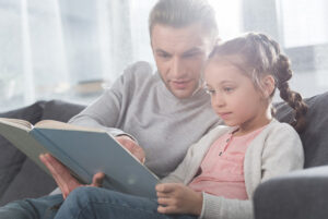 father teaching daughter to read