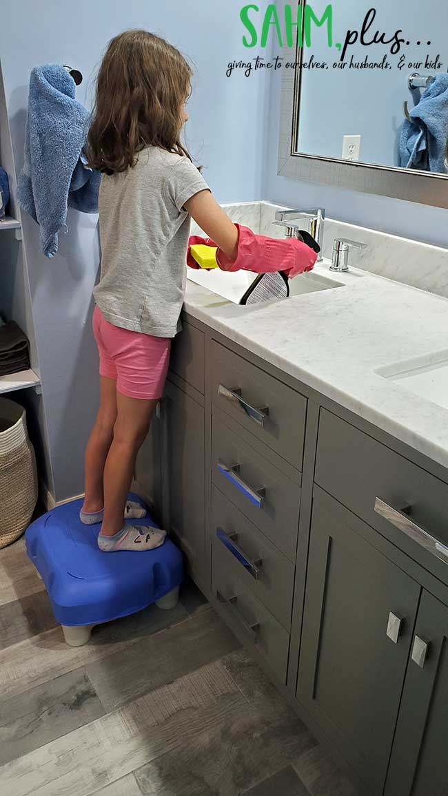 girl cleaning bathroom sink for chores