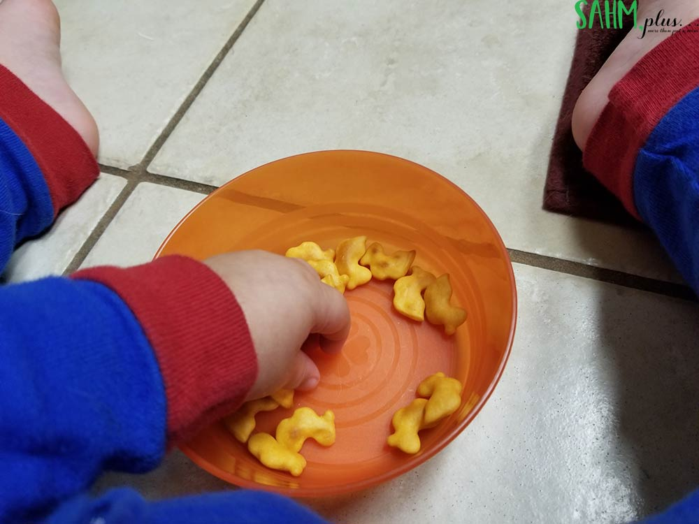 toddler hand in bowl of Brandless organic cheese duck crackers non-gmo snack