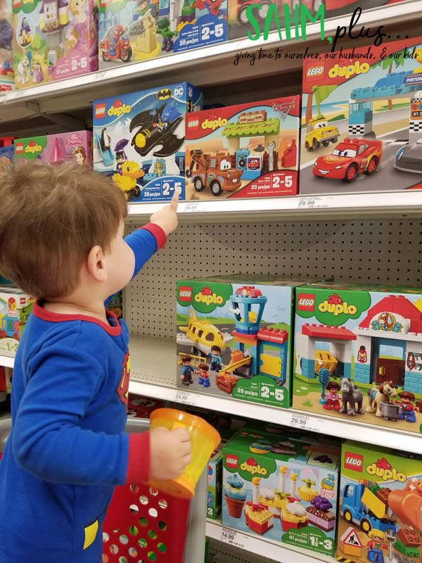 3 year old gift guide, picking out lego duplo at the store | sahmplus.com