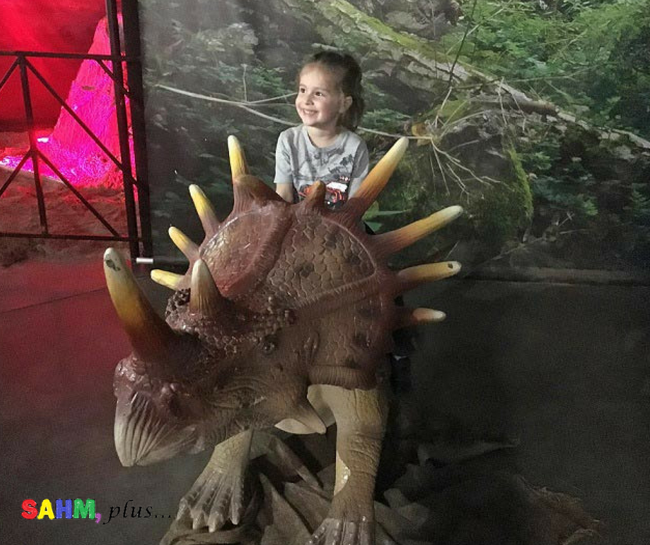 S sitting on a dinosaur at Jurassic Quest Jacksonville, FL