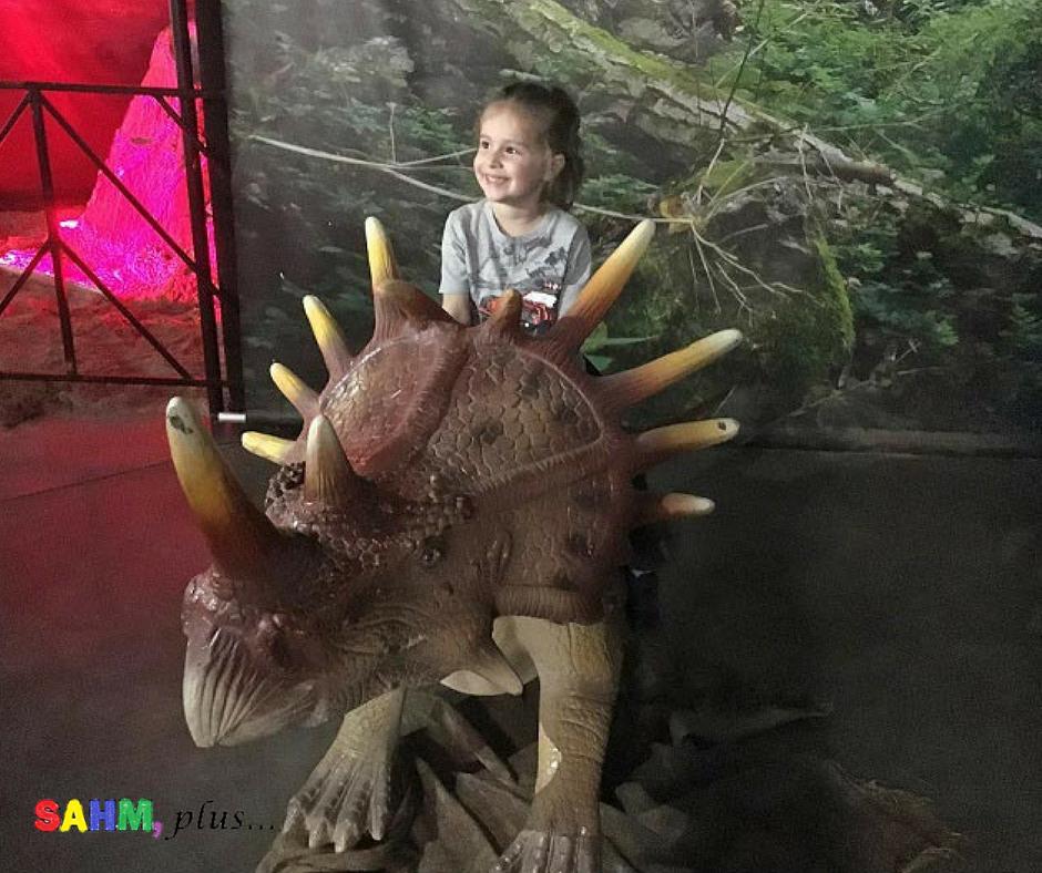 S sitting on a dinosaur at Jurassic Quest Jacksonville, FL