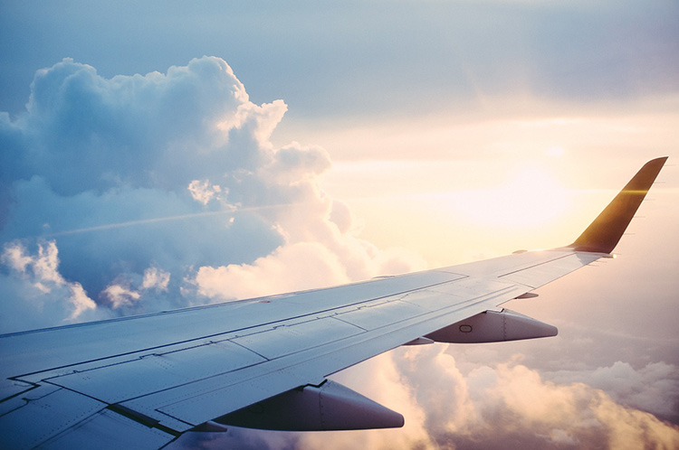 wing of plane in the clouds ; book your own flight or use a travel agent?