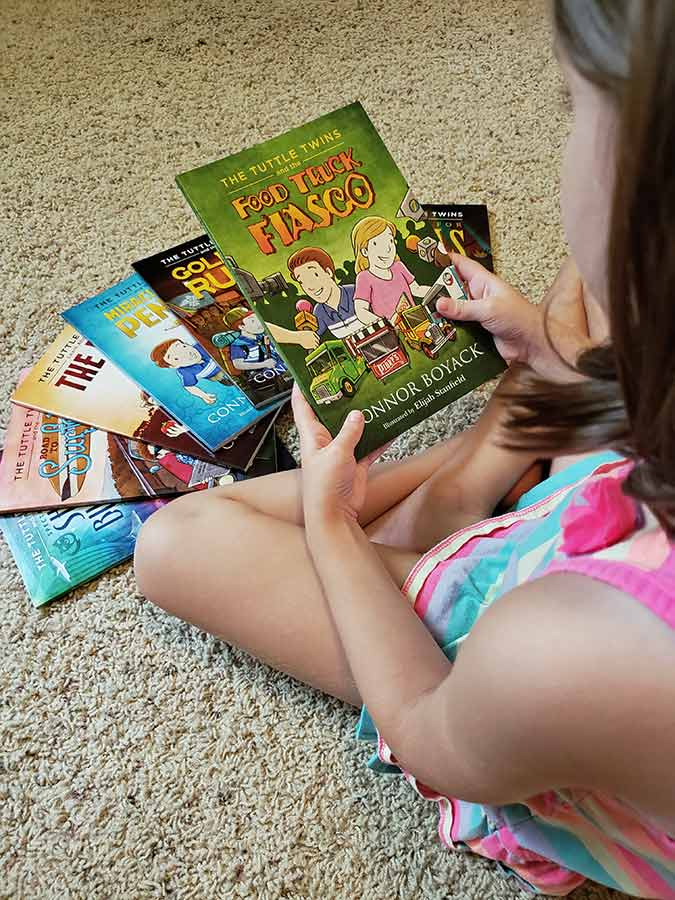 child looking at a The Tuttle Twins book in the series | sahmplus.com