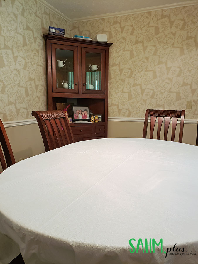 Table with white table linens and corner hutch in background | sahmplus.com
