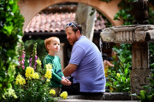 father talking to son at fountain