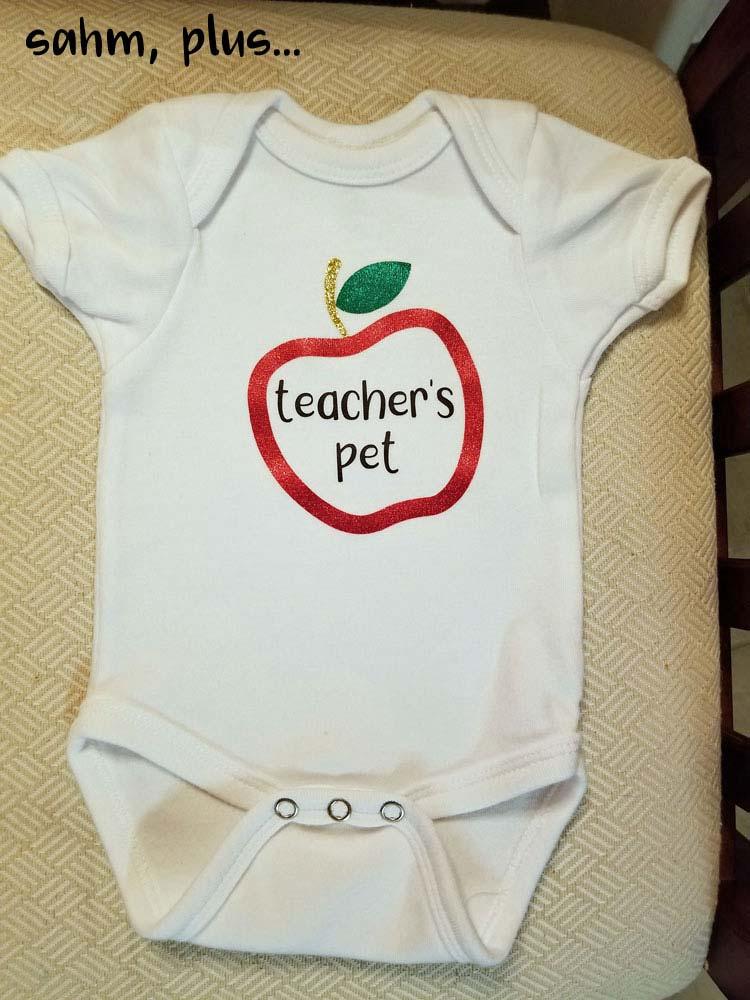 "This newborn baby bodysuit says ""teacher's pet"" inside a glitter monogram apple. Makes a perfect teacher's maternity leave or baby shower gift. | www.sahmplus.com"