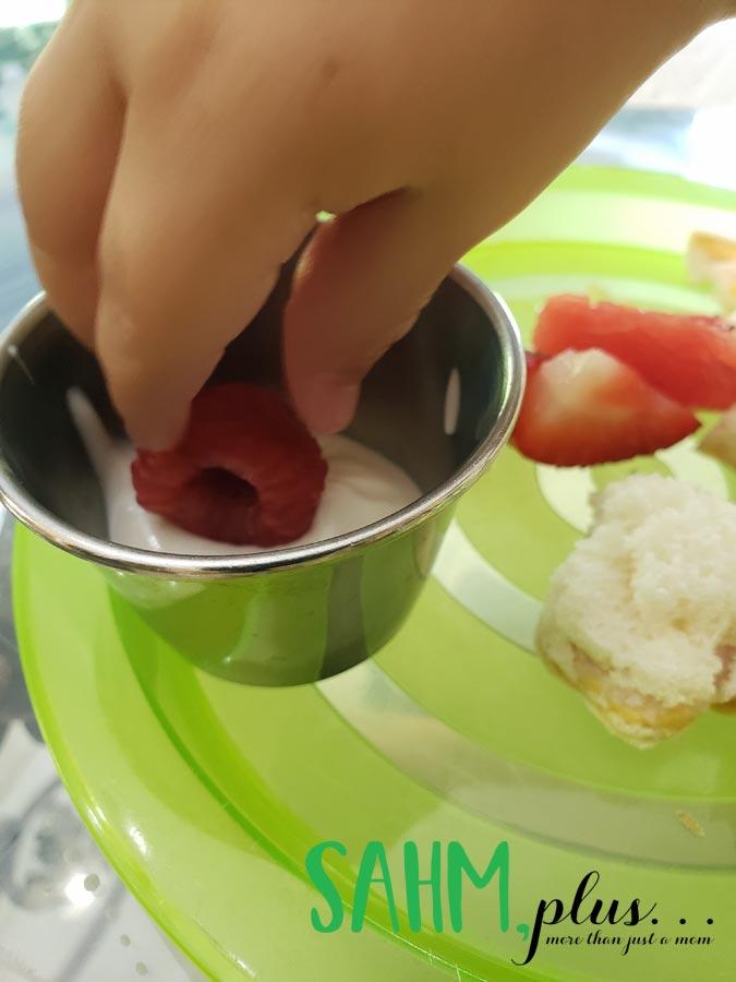 Toddler's hand dipping raspberry into vanilla yogurt   sahmplus.com
