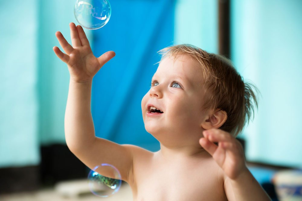 Toddler with bubbles - great outdoor activity for toddlers