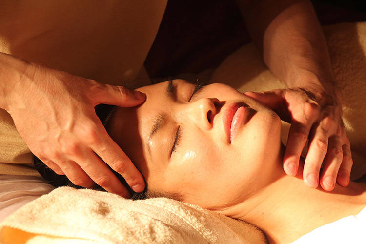 mom pampering herself with a face massage