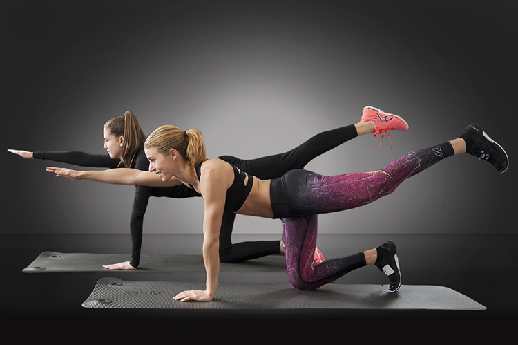 2 women doing a yoga pose