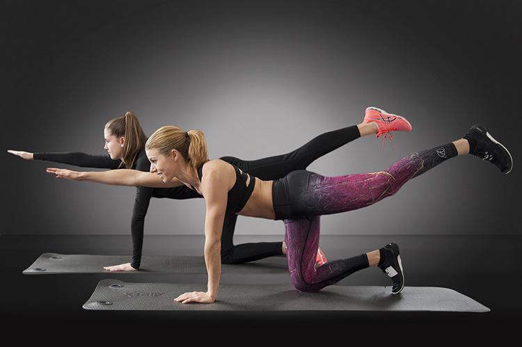 2 women doing a yoga pose